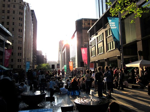 A peaceful crowd of people gathered at Martin Place in Sydney. Tall buildings to the left and right. A low setting sun illuminates the space.