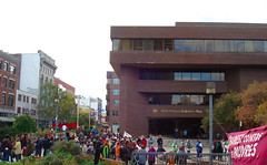 Photo de la foule où on voit le devant de la Bibliothèque Gabrielle-Roy ainsi que la bannière Charest contre les pauvres