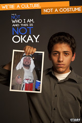 A young, presumably Arab, unsmiling man holds up a picture of a young, jovial white man dressed as a suicide bomber for Halloween. The poster reads We're a culture, not a costume. This is not who I am and it is not okay.