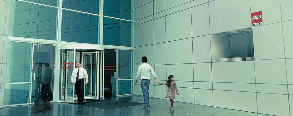 Fotografía de un padre y su hija entrando a un edificio de oficinas en el que hay un anuncio de LEGO en una pared, que simula ser un ladrillo de LEGO en mitad de un muro real