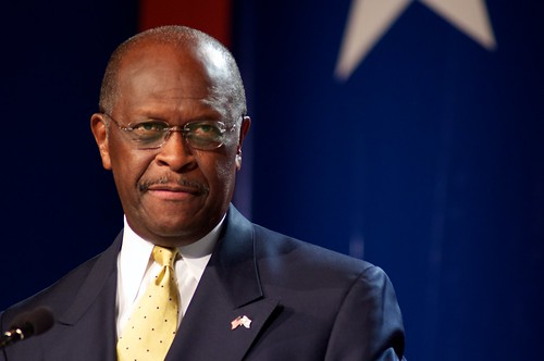 herman cain looks at the crowd