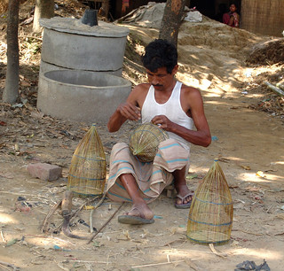 Bangladeshi man making a fish trap. Photo by WorldFish, 2006