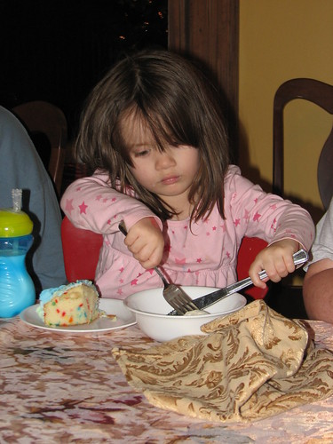 cutting her ice cream into bite-size pieces