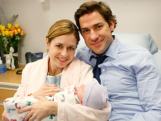 Pam and Jim holding their baby and looking at the camera