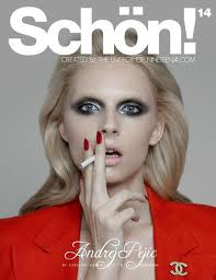 andrej pejic on the cover of schon magazine smoking a cigarette and wearing a red blazer with a chanel brooch