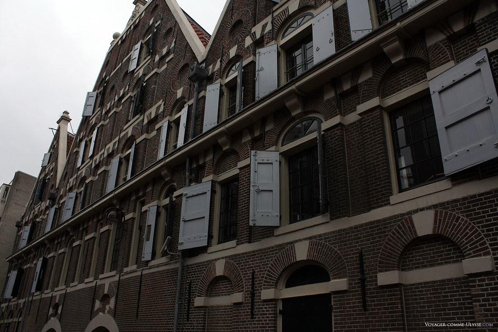 Façade d'un immeuble en brique, avec ses nombreux volets.