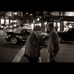 Walking harmonica player (In my entirety) Tags: street old light white playing man black night canon photography rebel 50mm town low instrument pasadena f18 ef harmonica xsi