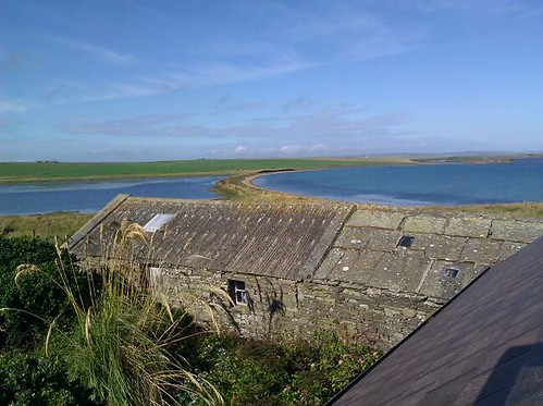View from upper floor of a house on the Orkney island of Shapinsay, looking north over an old stone barn to a curved blue bay under a blue sky