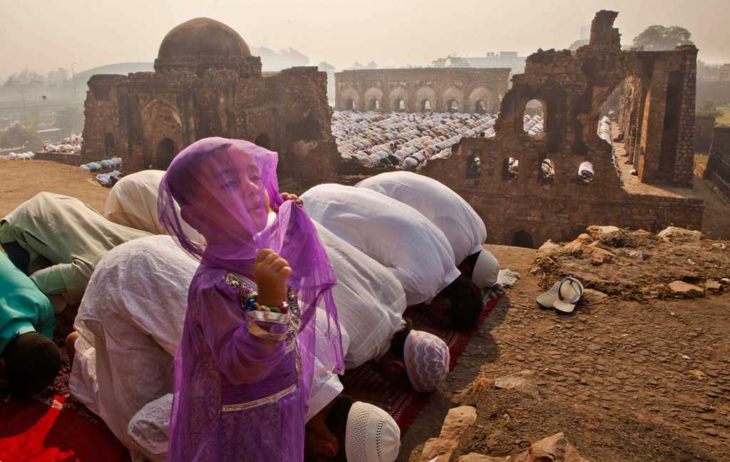 A young Indian Muslim girl gestures as others offer prayers during Eid al-Adha in New Delhi