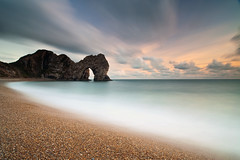 Durdle Door (peterspencer49) Tags: longexposure sea seascape southwest clouds sunrise movement arch unitedkingdom pebbles dorset coastline archway seaview coastalpath westcountry seaarch southwestcoast durdledoor jurassiccoast southwestcoastalpath seascene cliffwalks 5dmkll peterspencer archseaview