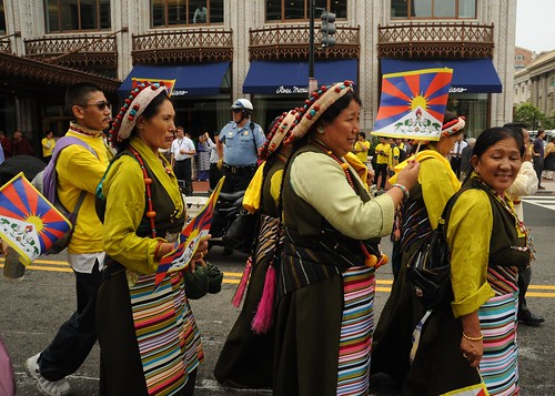 Tibetan woman in traditional chubas, head-dress of pearl, coral, turquoise, holding Tibetan national flag, HH Dalai Lama Birthday Peace Parade, Tibetans at Kalachakra, Washington D.C., USA by Wonderlane