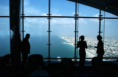 Tourists stand at the windows in the bar on the top floor of the Burj Al Arab Hotel