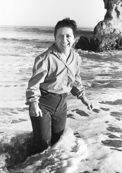 anzaldua in a black and white photo splashing on the beach