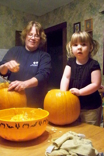 Grandma and Lucy scoop out pumpkin guts