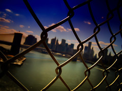Across the Wire -Lower Manhattan- (Yohsuke_NIKON_Japan) Tags: usa newyork pen river wire bokeh manhattan bluesky olympus pinhole brooklynbridge manhattanbridge eastriver wallstreet アメリカ ニューヨーク 川 オリンパス ボケ explored colorefex 金網 マンハッタン ワイヤー イーストリバー epl2