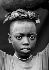 Menit tribe boy with scars on the face - Tum Ethiopia (Eric Lafforgue) Tags: africa boy people blackandwhite face look childhood vertical blackbackground youth person kid child noiretblanc market interieur portait headshot jeunesse indoors innocence jar omovalley inside marketplace ethiopia enfant tum naivete personne humanbeing marche scars scarification tete visage regard contemplation afrique jarre omo eastafrica garcon enfance abyssinia ethiopie darkbackground lookingatcamera traditionalclothes cicatrices toum blackandwhitepicture dedans abyssinie menit 0675 afriquedelest etrehumain vueinterieure habittraditionnel photoennoiretblanc meinit valleedelomo regardantlobjectif peoplesoftheomovalley peuplesdelavalleedelomo habittraditionnels peuplemenit menitpeople tribudesmenits menittribe meinitpeople meinittribe