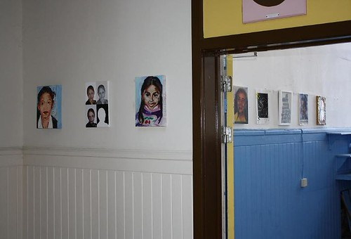wide shot of a gallery with four small paintings of women hanging on the wall in one room and several more in the next