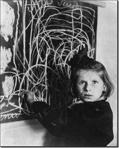 black and white photo of a girl scribbling on a chalkboard