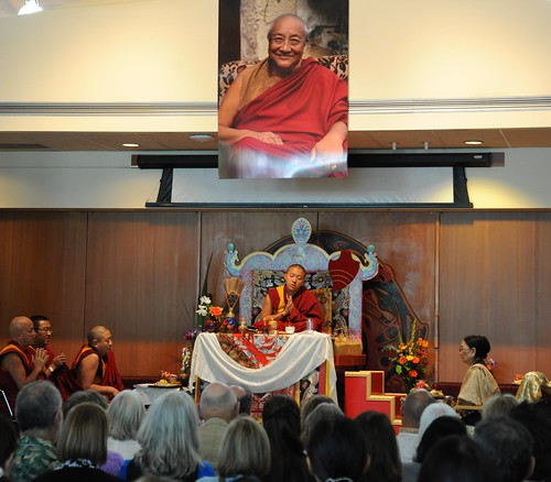 Dilgo Khyentse Yangsi Rinpoche saying prayers, throne, a photograph of his prior incarnation above, Dagmo Kushog Sakya (on the right), (monks on left) Rabjam Rinpoche, Changling Rinpoche, Mathieu Ricard, Vancouver BC, on stage, Lotus Speech Canada by Wonderlane