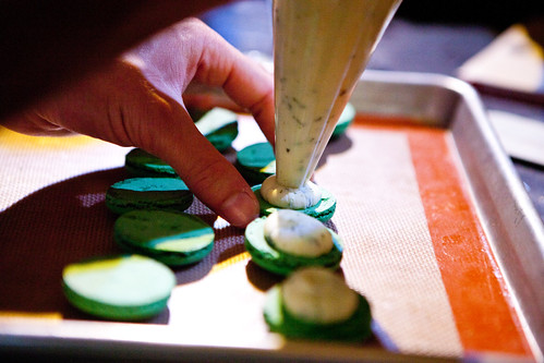 Piping out the mint ganache filling onto the macarons