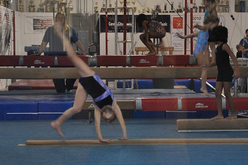 Alana practices a cartwheel on the low beam