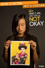 A young, unsmiling, Asian woman looks down at a picture of a white person dressed as a stereotypical Geisha. The poster reads We're a culture, not a costume. This is not who I am and it is not okay.