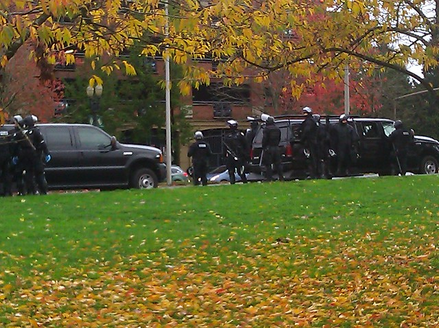 Police in riot gear wait for the arriving Occupy march in Waterfront Part, Portland, on a damp fall day