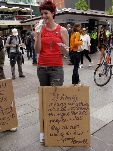 A woman standing with a sign reading, 'If liberty means anything at all, it means the right to tell people what they do not want to hear. - George Orwell'