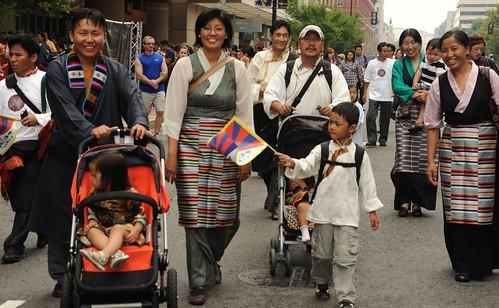 Big smiles - Tibetan families walking down the street, boy holding a Tibetan national flag, wearing traditional chubas, Happy Birthday to His Holiness the Dalai Lama Parade, Tibetans at Kalachakra, Washington D.C., USA by Wonderlane