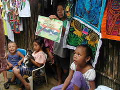 Children of San Blas with mola on display (D70) Tags: 2003 cruise family girls pet cat children island for this bigeyes san sale drawing earring caribbean panama articles sanblas embroidered income blas mola helping archipelago youngsters caribbeansea kunaindians