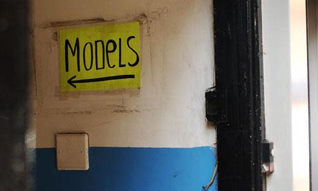 sign on a wall reading models, with an arrow