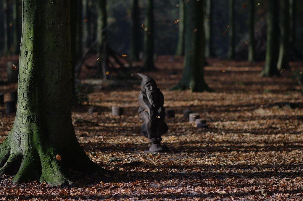 wooden gnome sculpture in falling leaves, Haagse Bos