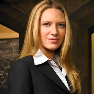 white woman with blond hair looking at the camera wearing a business suit