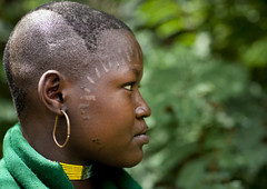 Menit woman with scarifications on the face, Tum market, Ethiopia (Eric Lafforgue) Tags: africa people haircut colour face horizontal youth outside outdoors person artistic market adolescente portait headshot jeunesse ornament teenager omovalley marketplace earrings bodypainting ethiopia hairstyle rite tum personne humanbeing marche scars scarification tete visage contemplation adornment coiffure afrique pigments dehors hairdress omo eastafrica 0997 abyssinia ethiopie bouclesdoreille exterieur coupedecheveux lookingatcamera traditionalclothes inprofile cicatrices toum deprofil abyssinie vueexterieure coloredpicture photocouleur afriquedelest traditionalhairstyle nomadicpeople etrehumain habittraditionnel valleedelomo regardantlobjectif peoplesoftheomovalley peuplesdelavalleedelomo coiffuretraditionelle colouredpicture habittraditionnels tummarket