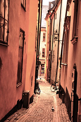 two bikes and a pigeon (my lala) Tags: street old red two town pigeon bikes gamlastan narrow stocholm
