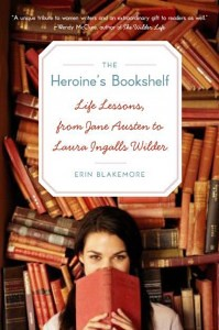 The cover of The Heroin's Bookshelf: Life Lessons, from Jane Austen to Laura Ingalls Wilder shows a photograph of a white woman with long brown hair holding an old book up over her face. Her back is facing a huge shelf covered in stacks of books, which take up the bulk of the cover