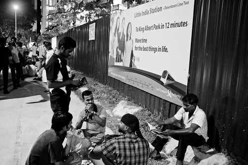 A group of foreign workers waiting outside the construction site for yet another train line.