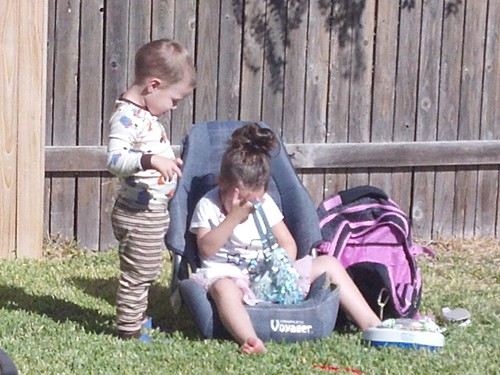 Daisy and Billy playing outside with a sequined purse, a carseat, and a backpack