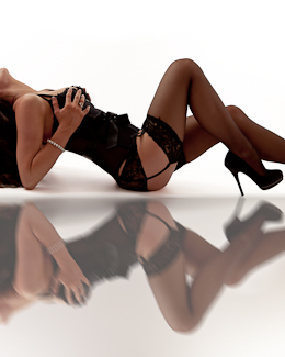 Erotic photograph of young woman wearing high heel shoes in sexy black lingerie.