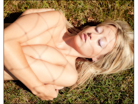 Glamour model posing topless on location.