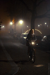 AMSTERDAM - November 22, 2011: Woman rides a city bicycle in the foggy Amsterdam at night (Max Mayorov) Tags: road street city travel portrait people urban woman holland netherlands amsterdam bicycle fog night dark lights cycling europe european cyclist ride illumination location riding destination lightning nederlands genre