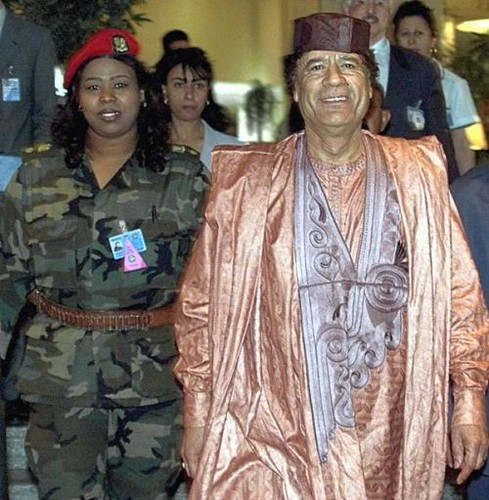 Libyan leader Col. Muammar Gaddafi with a woman bodyguard. A new radio station has been launched to encourage the resistance to the US-NATO puppet regime now occupying the North African state. by Pan-African News Wire File Photos