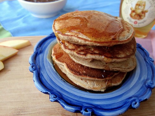 A stack of five pancakes, covered in maple syrup, sit on a blue plate. To the left are three slices of apples. In the background is a bowl of chocolate chia pudding and a bottle of ginger syrup.