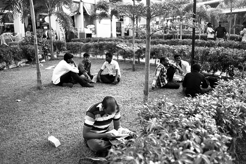 Men lounging in an open area, Little India, Singapore