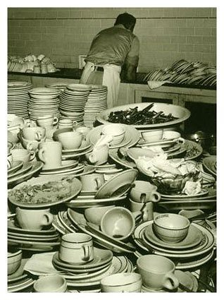 black and white photo of a man washing a huge pile of dishes