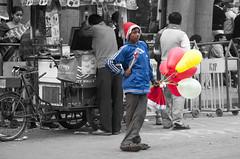 1 (Tapas Biswas) Tags: road christmas street blue girls boy people india color monochrome festival standing walking stand blackwhite nikon walk candid baloon think streetlife celebration thinking vendor kolkata bengal seller baloonseller colourb nikond90