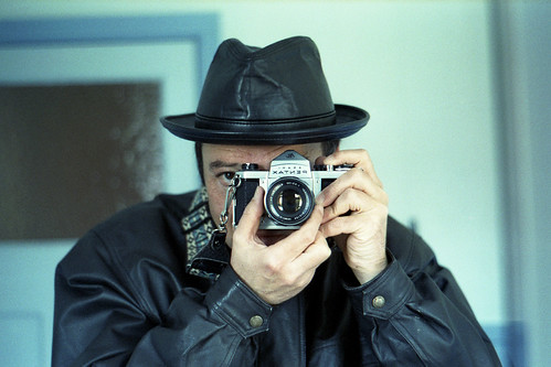 reflected self-portrait with Pentax S1 camera and leather hat by pho-Tony