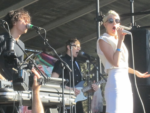 Three members of the band YACHT on stage. Claire Evans is caught mid-note, her mouth making a dramatic O as she sings into the mic