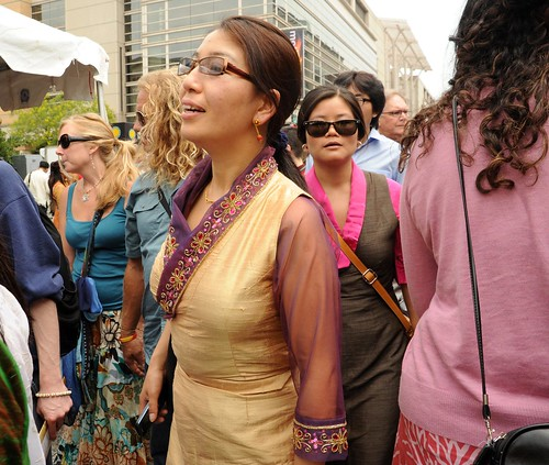 Contemporary Tibetan Chuba design of gold silk, fancy detail on collar and cuffs, Tibetan woman make their way through the crowd, Kalachakra for World Peace, Happy Birthday to the Dalai Lama Parade, Washington D.C., USA by Wonderlane