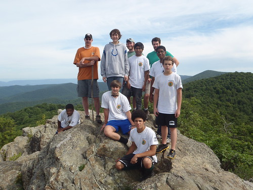 "Park Manager Tony Widmer (orange shirt) poses with the Shenandoah River State Park YCC crew in the obligatory ""crew stands on rocks"" picture for programs in the mountain parks."